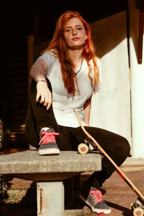Woman in White Shirt and Black Pants Sitting on Concrete Bench