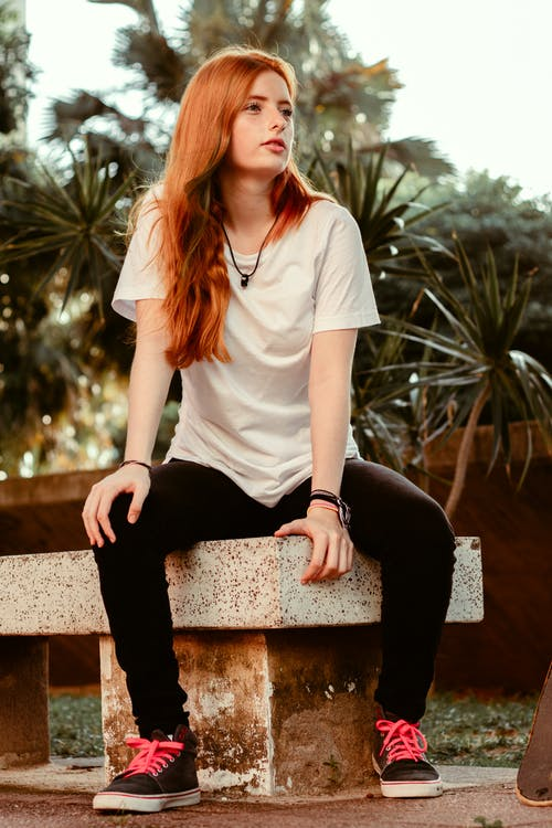 Woman in White Crew Neck T-shirt and Black Pants Sitting on Brown Concrete Bench during