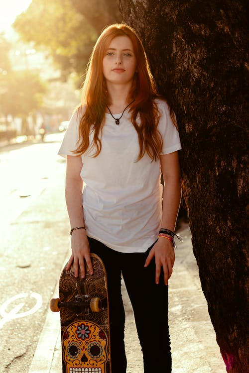 Woman in White Shirt and Black Pants Standing Beside Tree