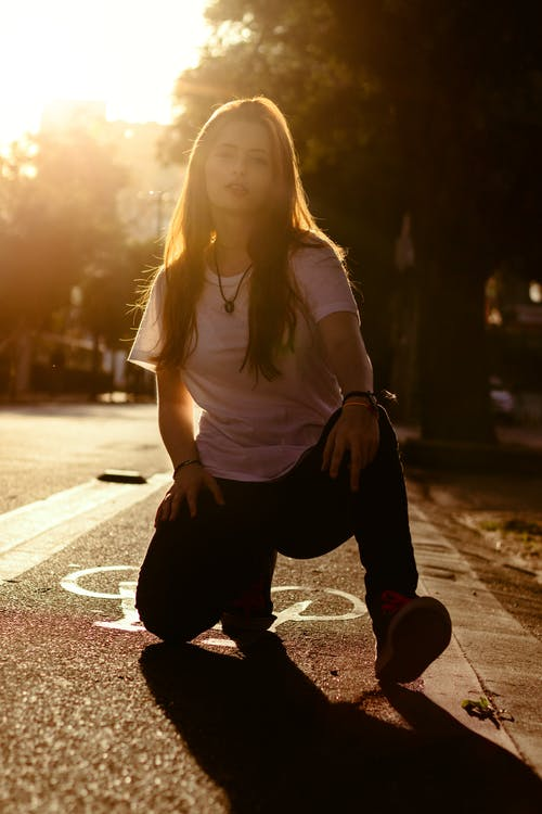 Woman in White Shirt and Black Pants Sitting on Road