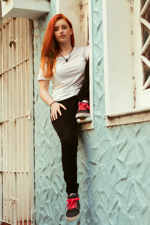 Woman in White Tank Top and Black Pants Standing Beside White Wooden Door
