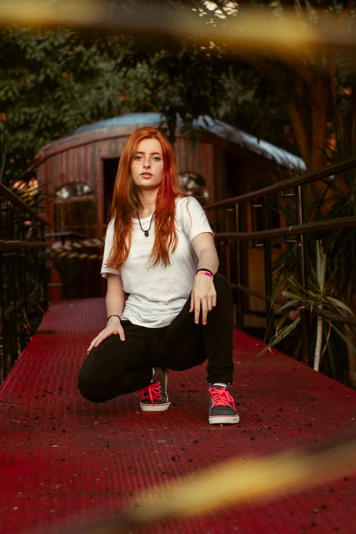 Woman in White Shirt and Black Pants Sitting on Red Wooden Bridge
