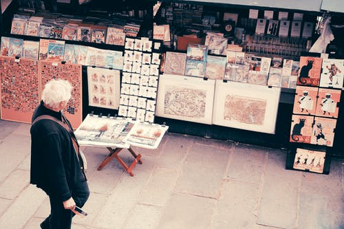 Photo of an Old Man Looking at the Pictures