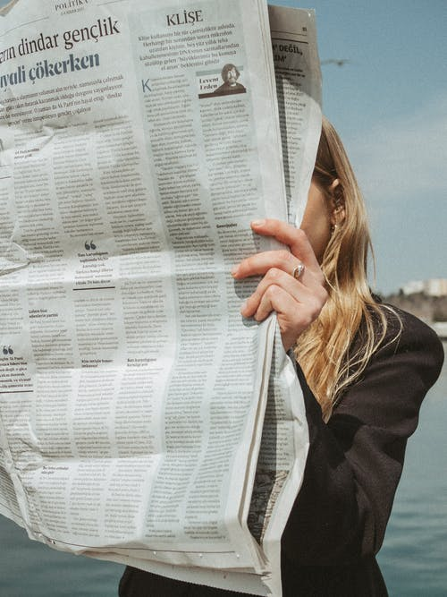 A Woman Reading a Newspaper Near Body of Water
