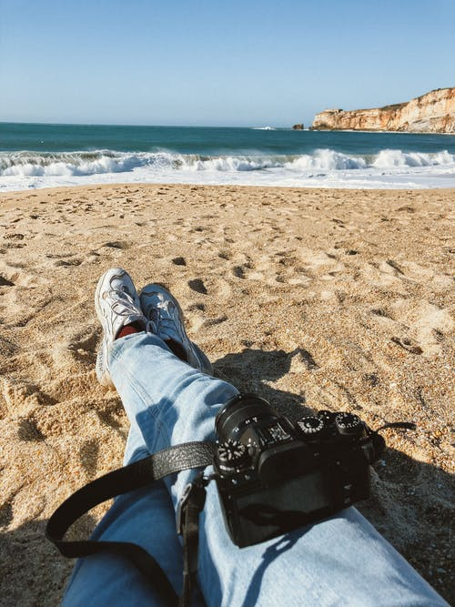 A Person in Blue Denim Jeans with Camera Sitting on the Sandy Beach