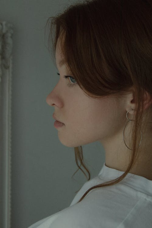 Side view of crop tranquil female with blue eyes wearing white shirt thoughtfully looking away