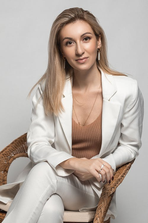 Charming woman with blond hair in stylish clothes sitting on armchair and looking at camera against light background in studio
