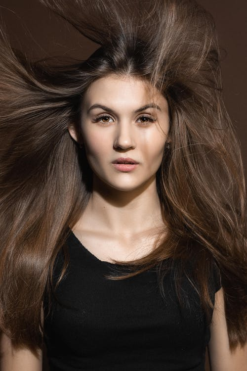 Serious woman with flying hair looking at camera