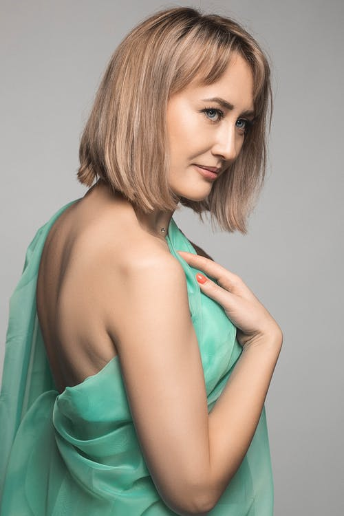 Side view of pensive female with short blond hair in light green dress looking away against light background in studio