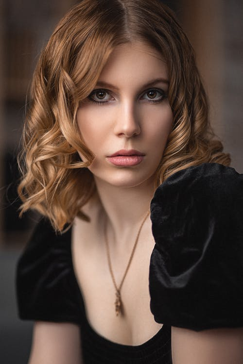 Pensive female with curly hair and stylish clothes looking at camera against blurred background in room