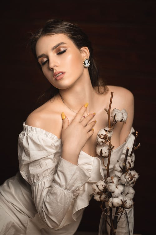Young charming female with dark hair and makeup wearing white dress with bare shoulders sitting with eyes closed near glass vase with decorative branches on black background