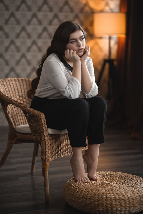 Full body of young female in casual clothes sitting on wicker chair leaning on hands and looking away while resting in dark cozy room