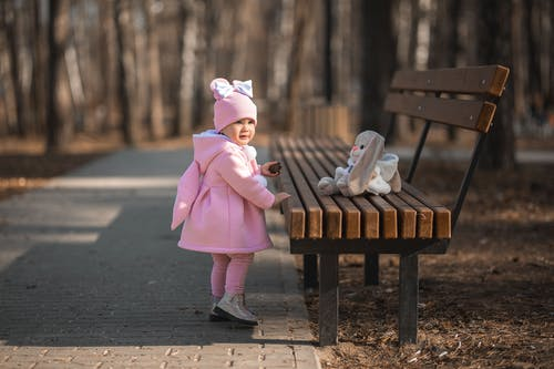 Full body of cute little girl in warm outfit standing near toy on wooden bench in park and looking away