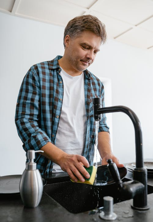 Man in a Black and Blue Checkered Shirt Washing the Dishes
