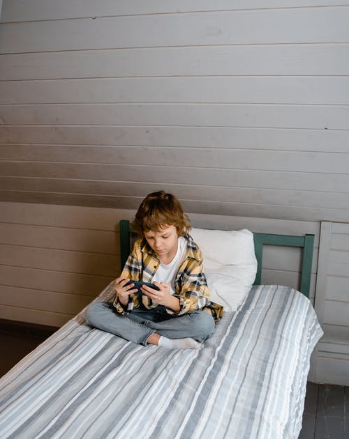 Boy in Yellow Shirt Sitting on Bed and Playing on Mobile Phone