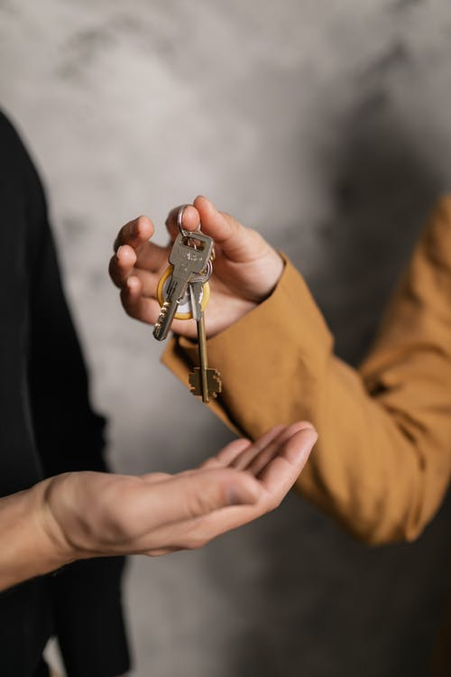 Person Holding Silver Keys With Silver and Gold Keys