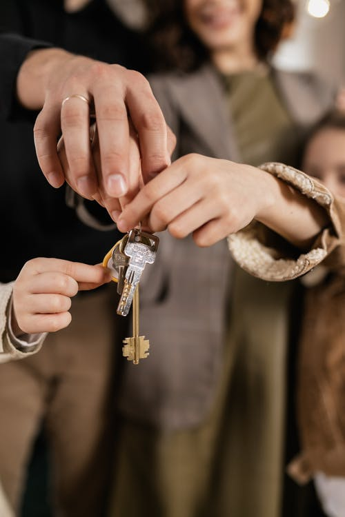 Person Holding Silver and Gold Key