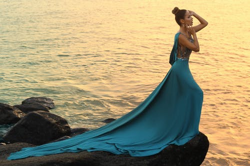 Woman in Blue Dress Standing on Rock Near Body of Water
