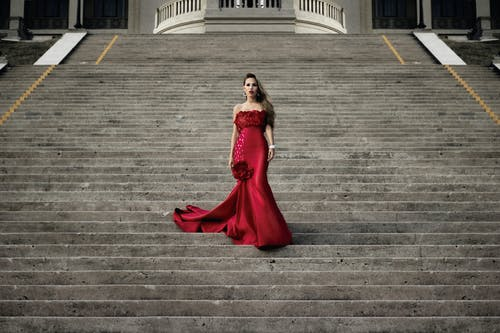Woman in Red Dress Standing on Stairs