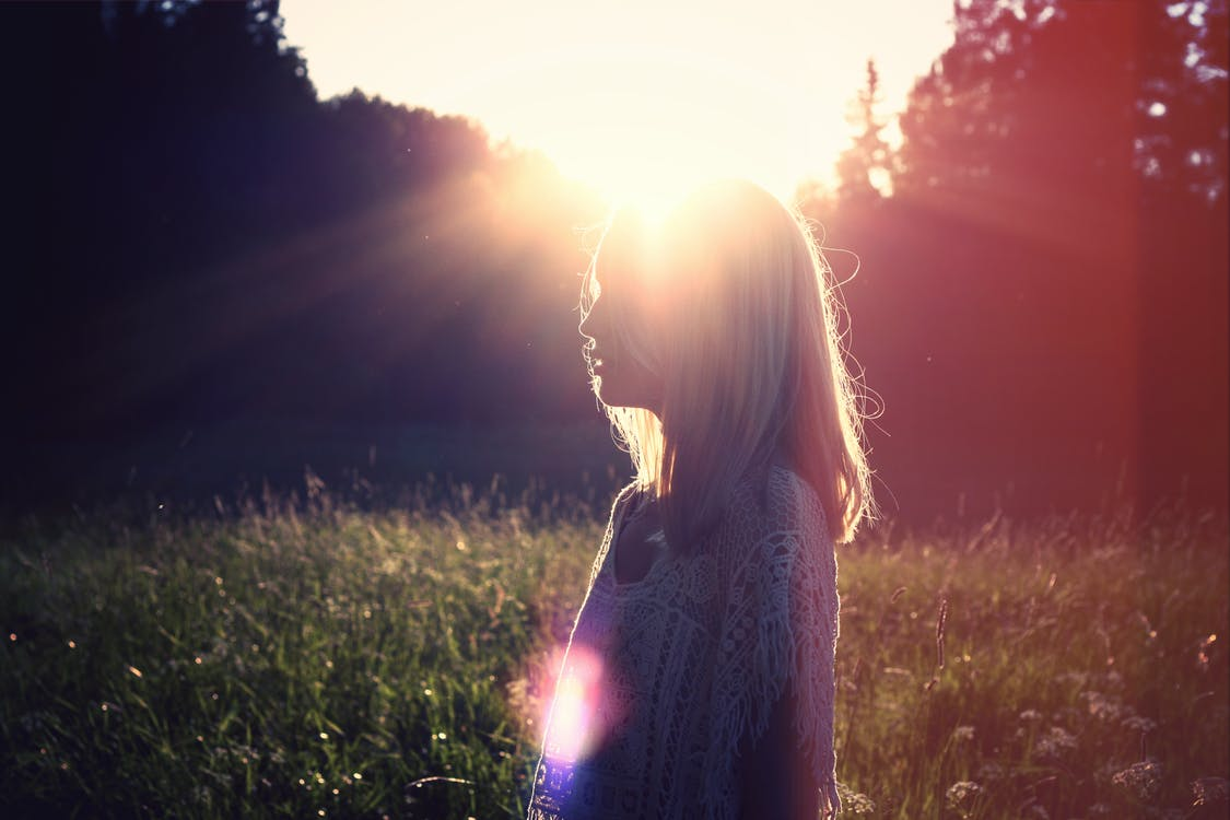 Woman Standing in Front of Sun