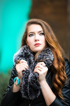 Photo of a Woman Holding Her Black Furry Scarf