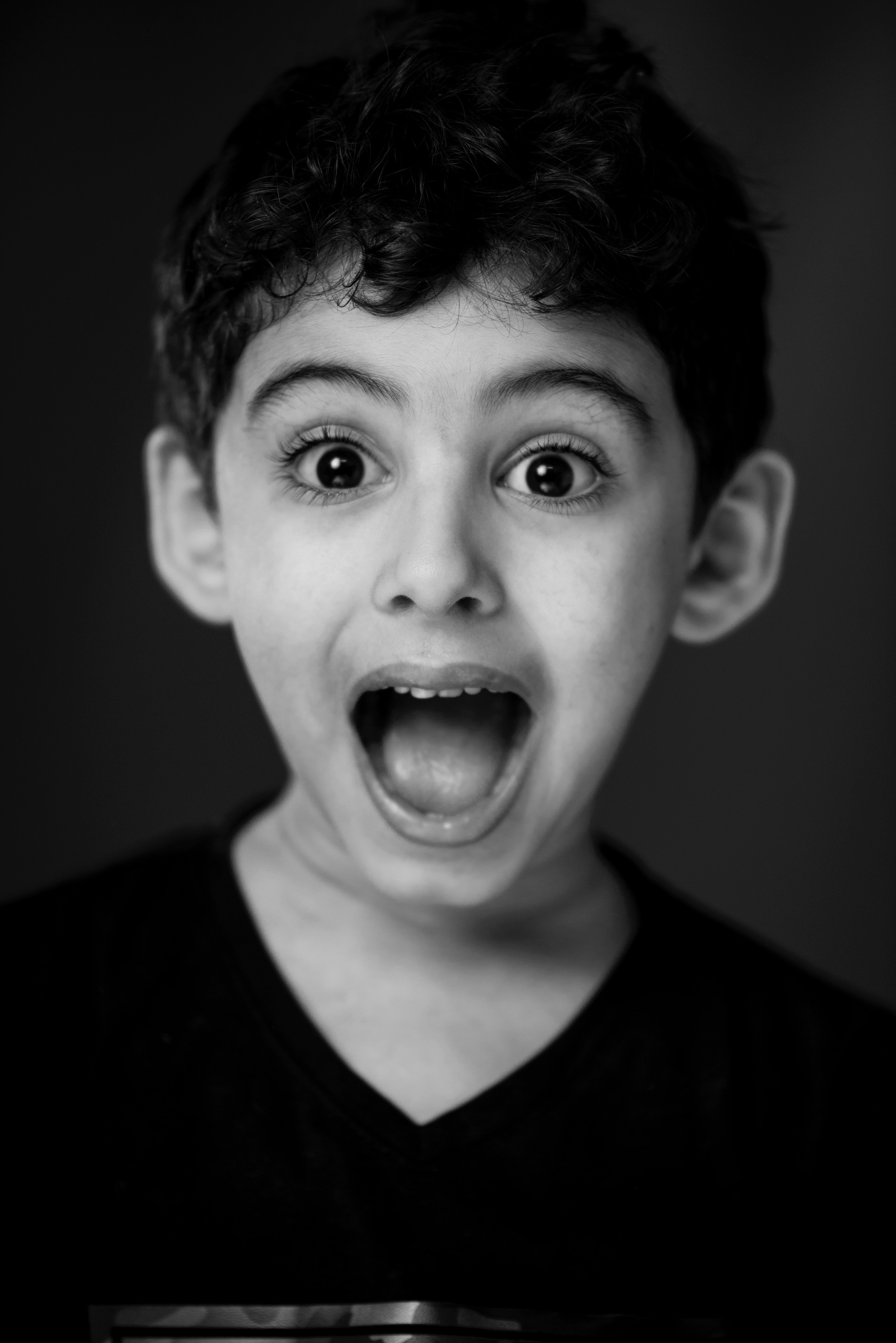 Boy in Black V-neck Shirt With Looking Straight to the Camera With a Shocking Face Expression