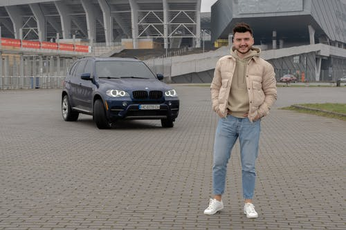 Man in Beige Jacket Standing Beside Black Bmw Car