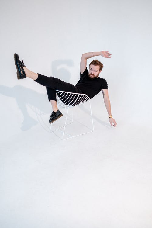 Man in Black T-shirt and Black Pants Sitting on White Chair