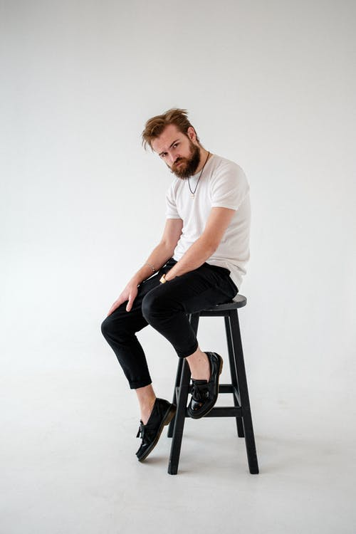 Man in White Crew Neck T-shirt and Black Pants Sitting on Black Seat