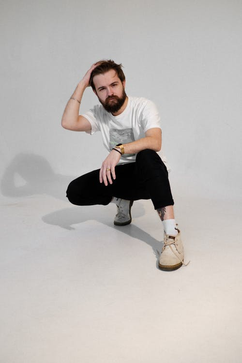 Man in White Crew Neck T-shirt and Black Pants Sitting on White Floor