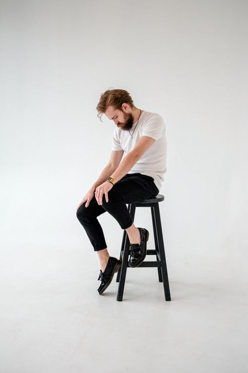 Woman in White T-shirt and Black Pants Sitting on Black Seat