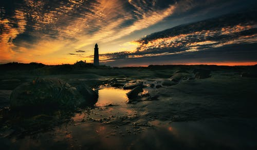 Silhouette of Lighthouse on Rocky Shore during Sunset