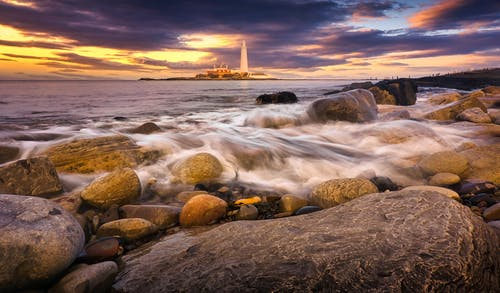 Rocky Shore With Rocks and Body of Water during Sunset
