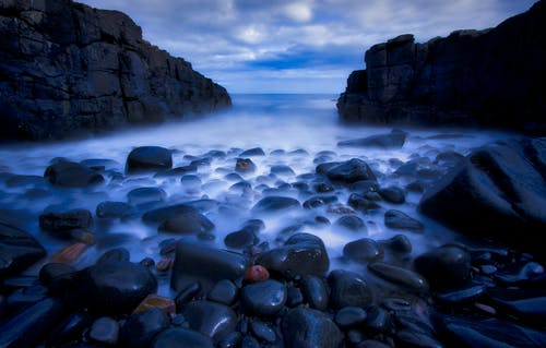 Rocky Shore With Rocks Under Cloudy Sky