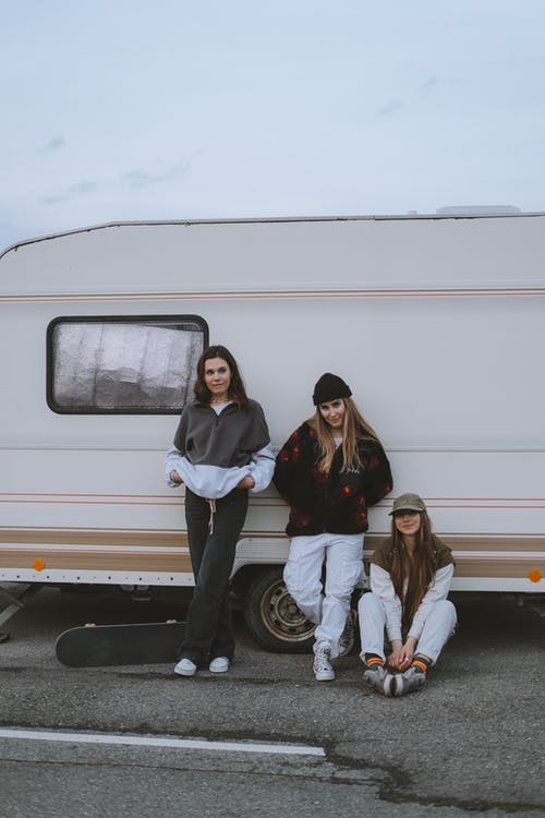 Young Women Leaning on a Caravan
