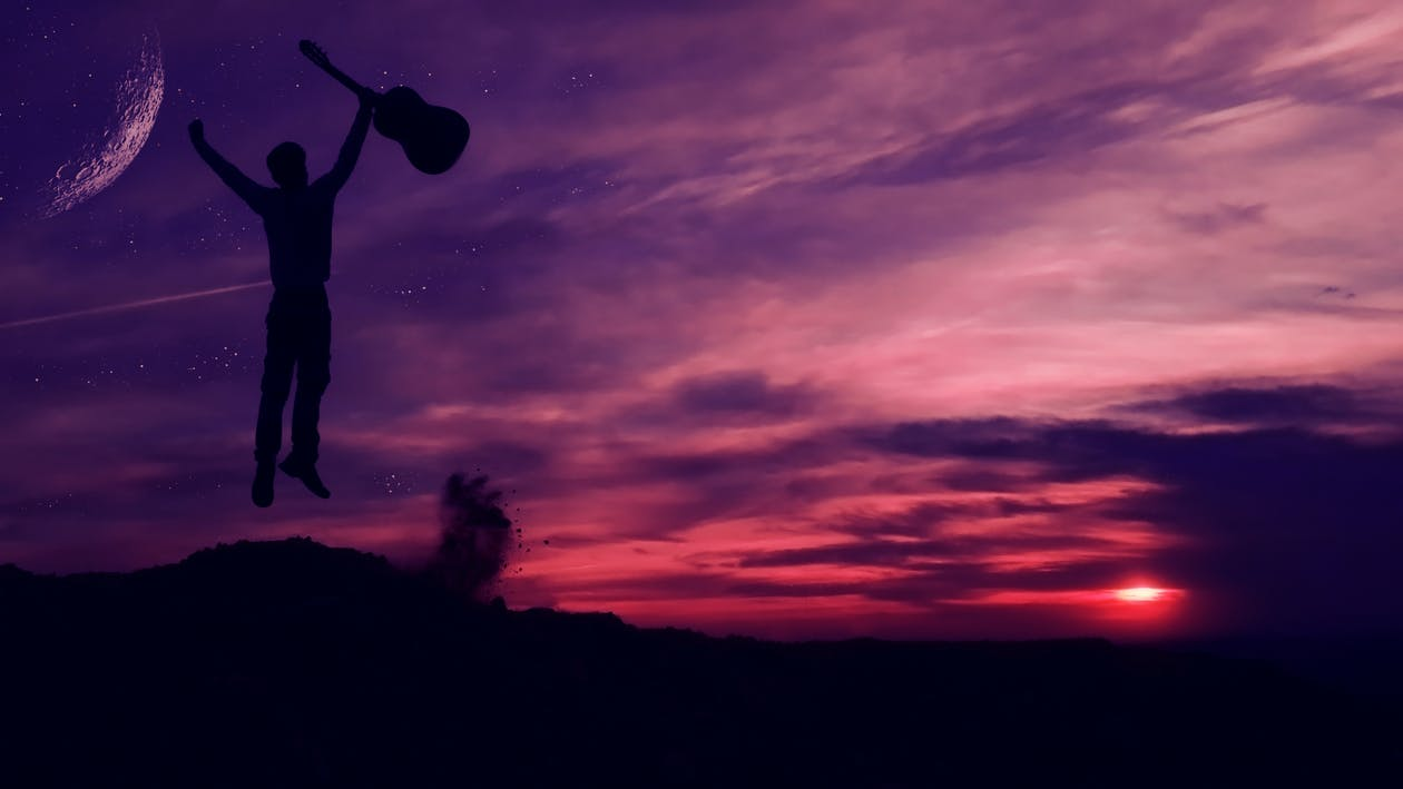 Silhouette of Man Holding a Guitar
