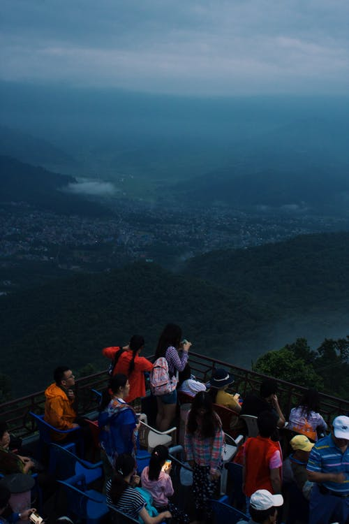 Group of People Looking at Mountain and City View