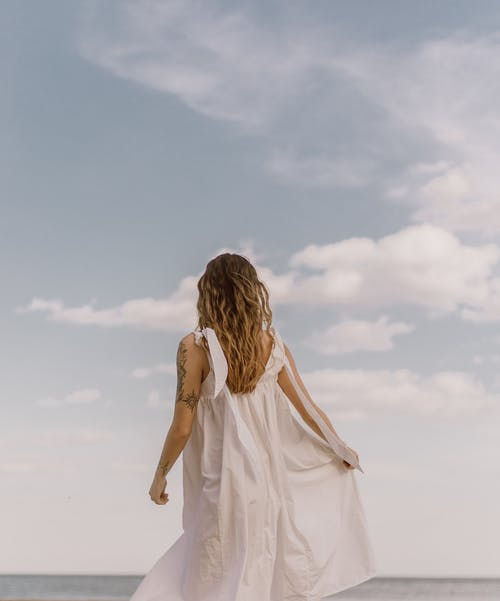 Unrecognizable tattooed woman admiring ocean under cloudy sky