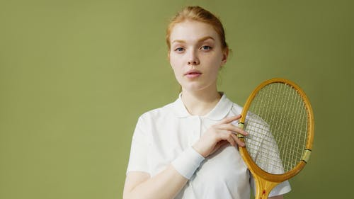 Young Woman in White T-Shirt Holding Tennis Racket