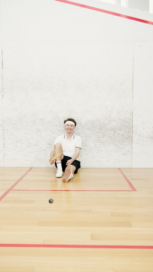 Man Smiling and Holding Tennis Racket While Sitting on the Floor