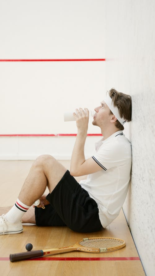 Man Drinking Water While Sitting on the Floor