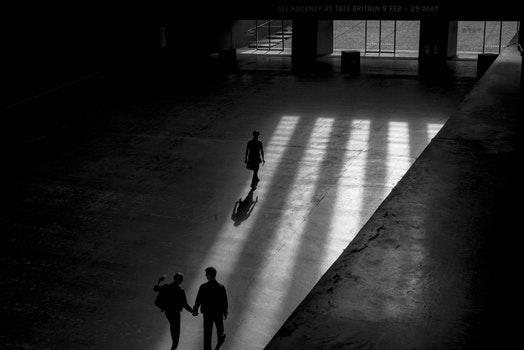 Grayscale Photo Of Three Men Walking Inside Building