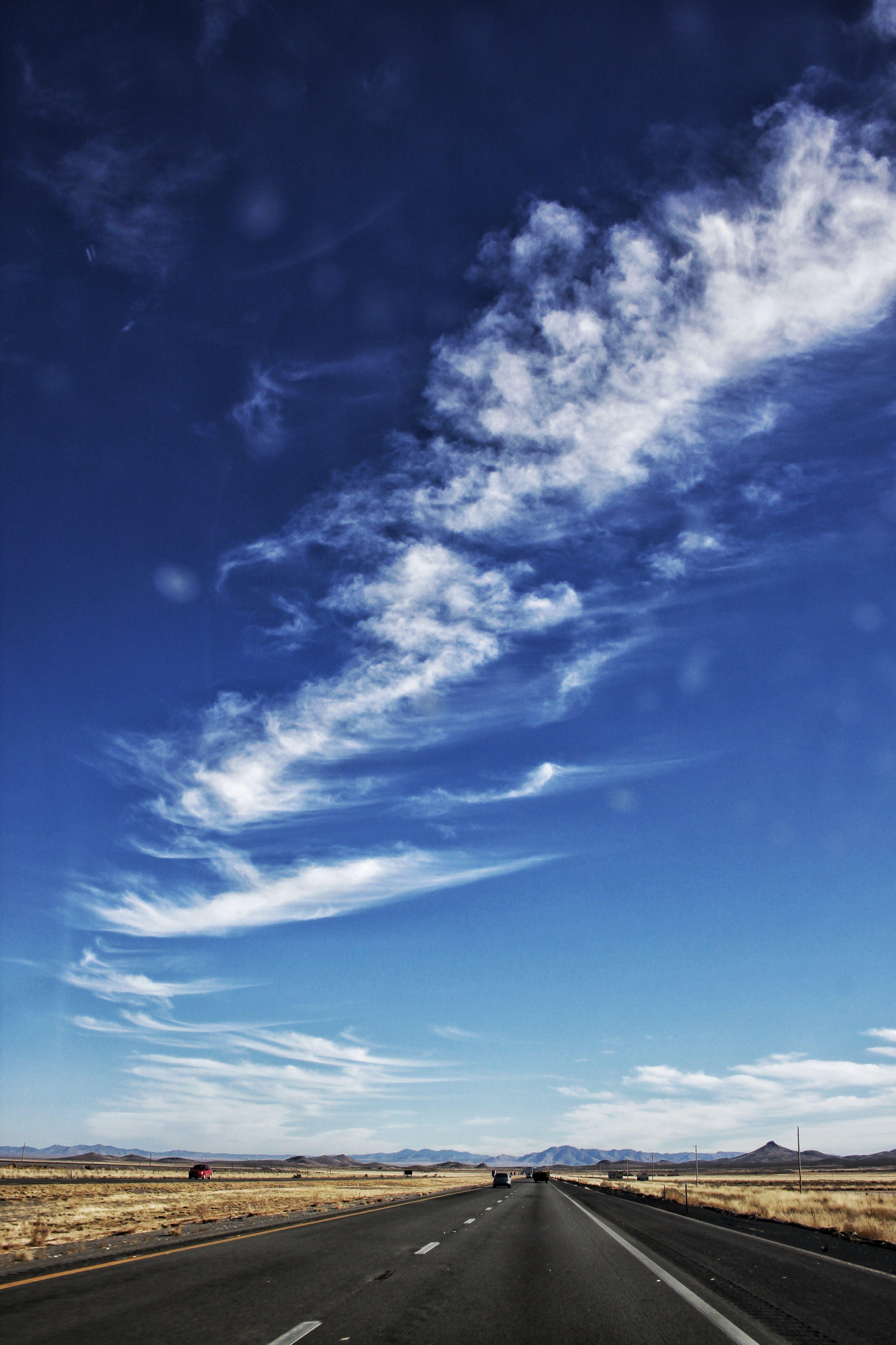 Cirrus Clouds over Empty Black Road