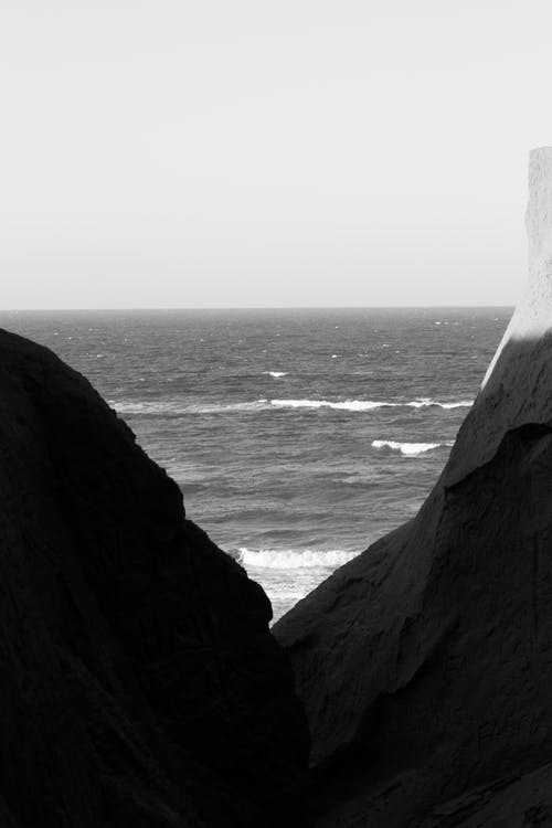 Grayscale Photo of Rocky Mountain by the Sea