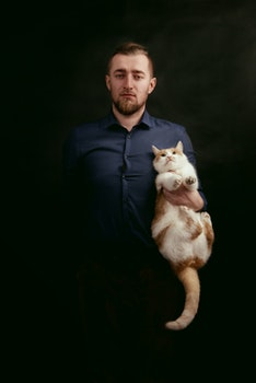 Man in Grey Dress Shirt Holding White and Orange Fur Cat