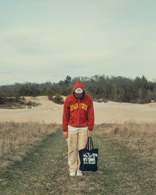 Man in Red Hoodie and Black Backpack Standing on Brown Field