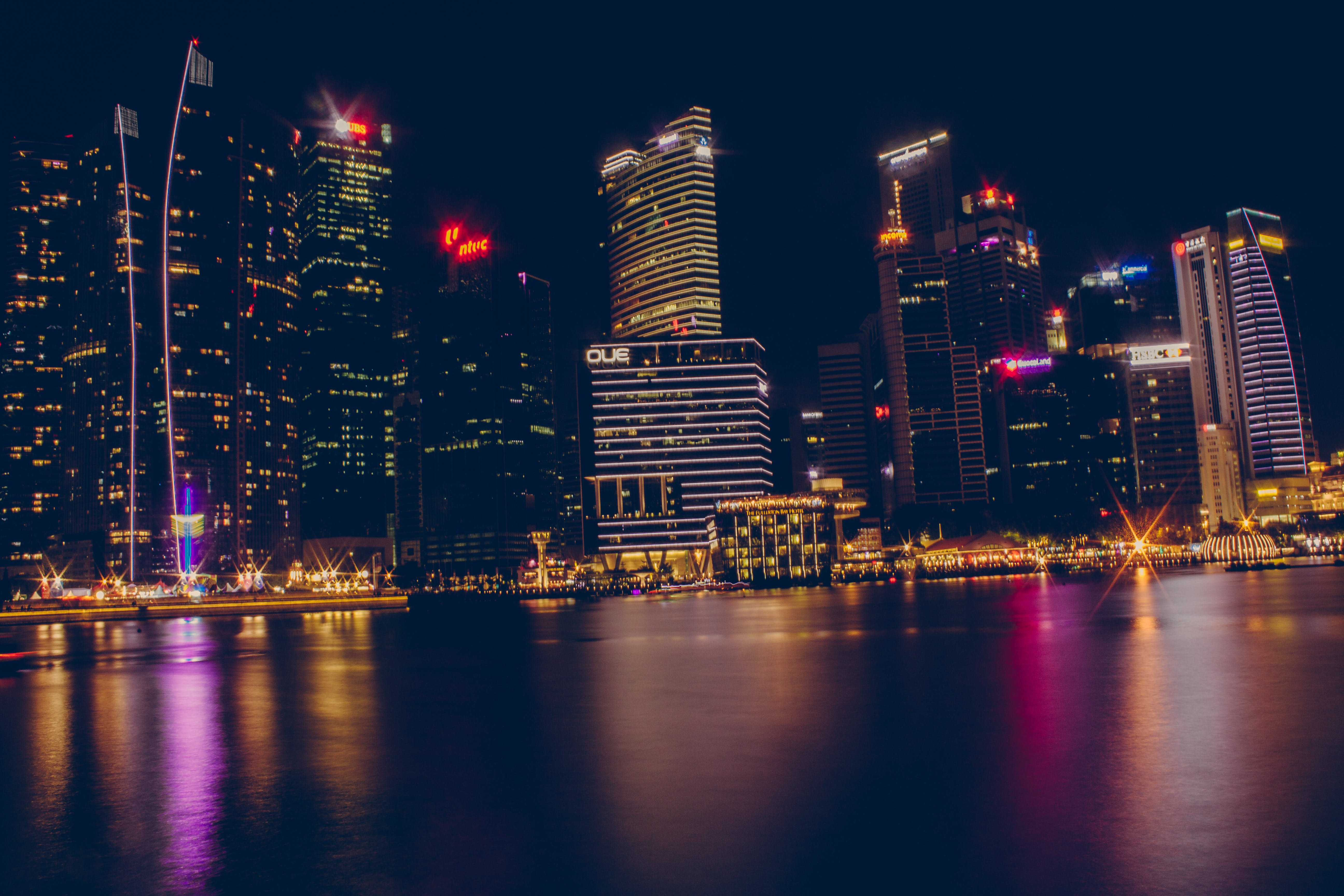 Buildings Near Body Of Water During Night Time