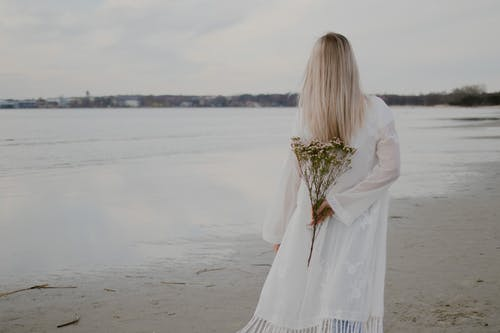 Woman in White Long Sleeve Dress Holding Bouquet of Flowers Standing on Beach Shore