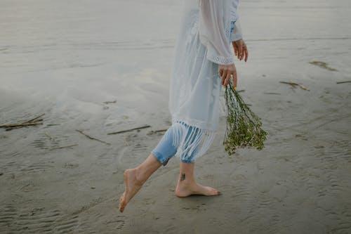 Woman in White Dress Walking on Beach