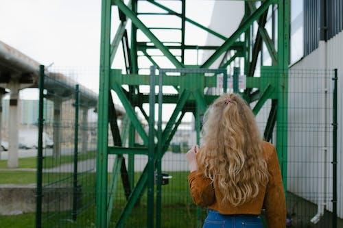 Woman in Blue Shirt Standing Near Green Metal Frame